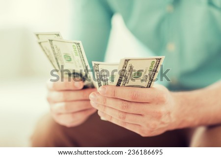 savings, finances, economy and home concept - close up of man counting money at home - stock photo
