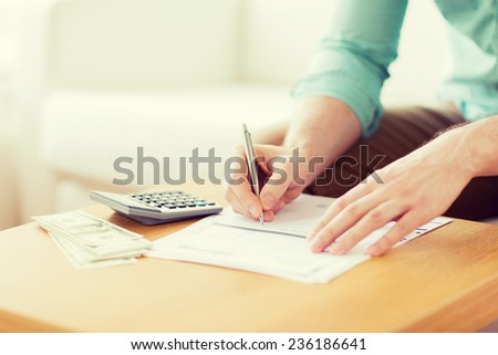 savings, finances, economy and home concept - close up of man with calculator counting money and making notes at home - stock photo
