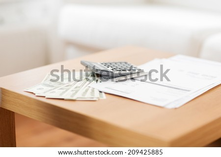 savings, finances, economy and home concept - close up of money with papers and calculator on table at home - stock photo