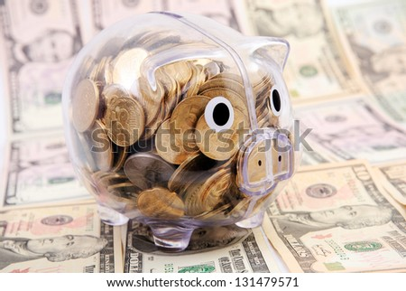 Savings in piggy bank isolated on the dollars banknote background