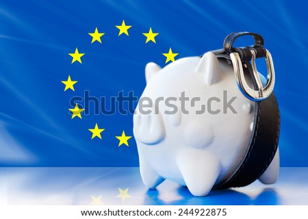 savings in piggy bank - tighten the belt - European union flag - stock photo