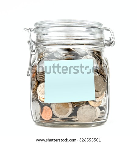 Savings money box coins thai baht with empty blue stick note paper isolated on white background. Jar for savings full of coins. Piggy bank for saving money template for text. Close up. Front view. - stock photo