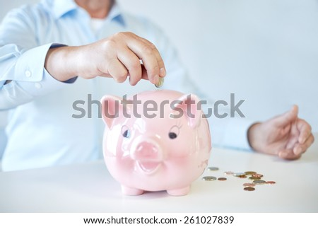 savings, oldness, business, people and banking concept - close up of senior man hands putting coins into piggy bank