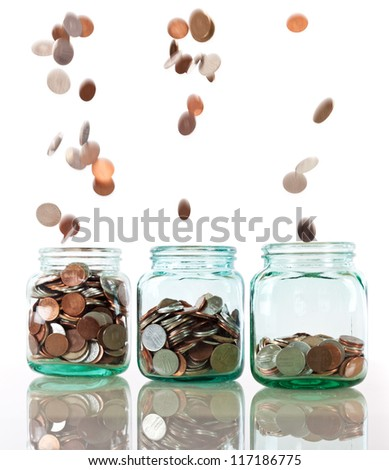 Savings rate concept - jars in row filling up with falling coins, focus on middle jar - stock photo