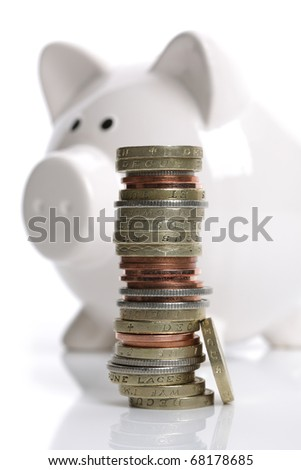 Savings stacked in front of a white piggy bank - stock photo