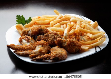 savoring a delicious plate of chicken sticks with fries  - stock photo