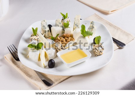 Savory appetizers garnished with fresh herbs served with cashew nuts and a savory creamy dipping sauce to be eaten as gourmet finger food - stock photo