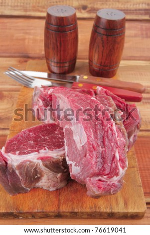 savory: bloody beef fillet (red meat) on wood with cutlery and castor - stock photo