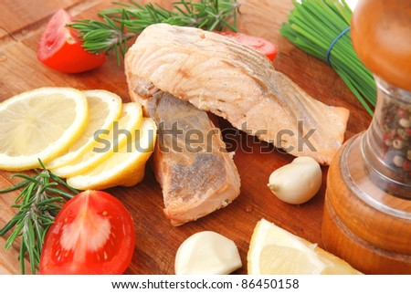 savory fish portion : grilled salmon fillet with green chinese onion, red cherry tomatoes , allspice pepper in grinder, rosemary twigs and lemon slice on wooden board isolated over white background