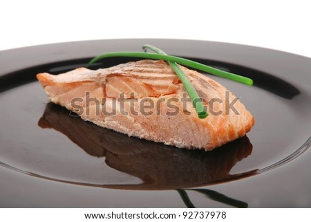 savory fish portion : norwegian salmon fillet roasted with green chinese onion, on black dish isolated over white background - stock photo