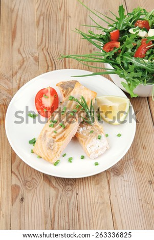 savory fish portion : roasted norwegian salmon chunks and vegetable salad on white dish over wooden table - stock photo