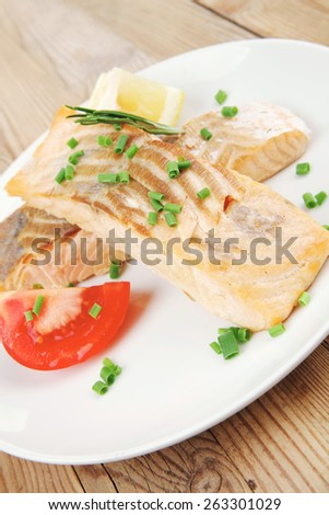 savory fish portion : roasted norwegian salmon chunks on white dish over wooden table - stock photo