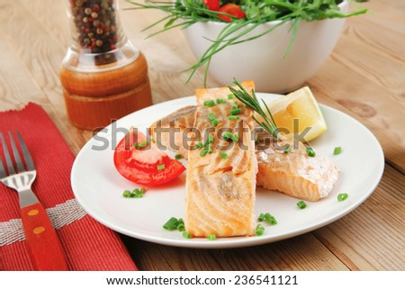 savory fish portion : roasted norwegian salmon chunks with  lemon and vegetable salad , rosemary twig and red caviar in white bowl over wooden table - stock photo
