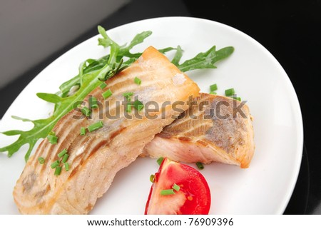 savory fish portion : roasted norwegian salmon fillet garnished with rocula leaves and tomatoes on white dish isolated over black background - stock photo
