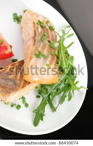 savory fish portion : roasted norwegian salmon fillet garnished with rocula leaves and tomatoes on white dish isolated over black background