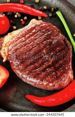 savory : grilled juicy beef steak served with hot cayenne peppers cherry tomato green chives on metal pan isolated over white background - stock photo