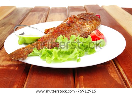 savory on plate : roast golden fish served on fish plate with lemon tomatoes and spices - stock photo