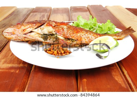 savory on wood: fried fish served with tomatoes lemon and spices - stock photo