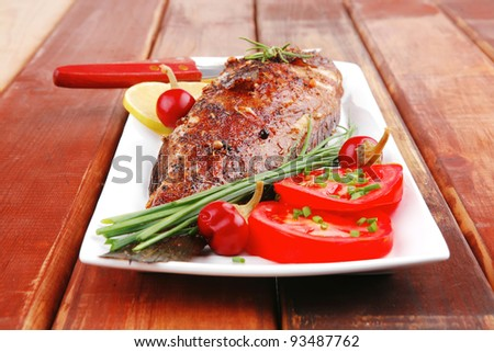 savory on wood: whole fryed sunfish over plate with tomatoes lemons and peppers - stock photo