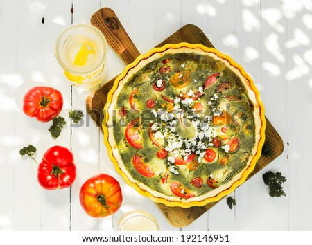 Savory quiche with egg, tomatoes, cheese and herbs viewed from above on a wooden chopping board with fresh tomatoes on a rustic white wooden table outdoors - stock photo