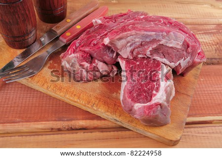 savory: red raw beef meat steak on wooden cutting board prepared for roasting