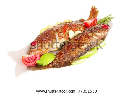 savory : roast golden fish served on fish plate with lemon tomatoes and rosemary - stock photo