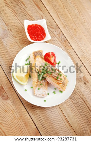 savory sea fish : baked salmon strips on white dish with red caviar over wooden table