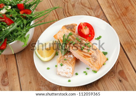 savory sea fish : baked salmon strips with vegetable salad on white dish over wooden table - stock photo
