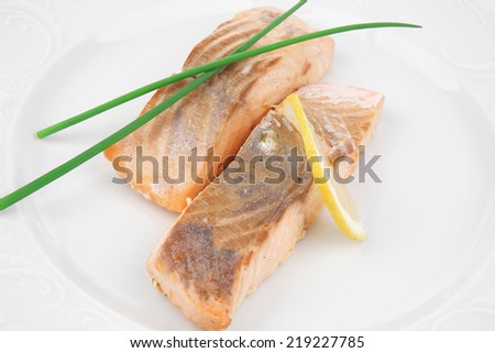 savory sea fish entree : roasted salmon fillet with green onion, and lemon on white plate isolated over white background - stock photo