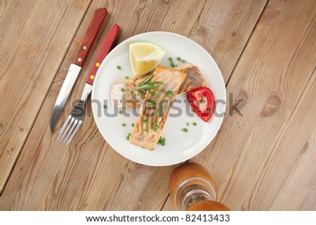 savory sea fish entree : roasted salmon fillet with green onion, red cherry tomatoes pieces, glass pepper grinder, rosemary twigs and lemon on wooden board