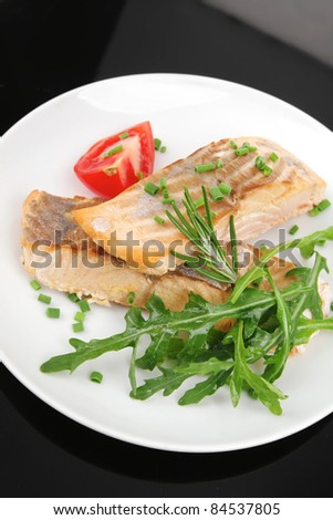 savory sea fish : roasted salmon fillet garnished with green rocket leaves and tomatoes on black dish isolated over black background - stock photo