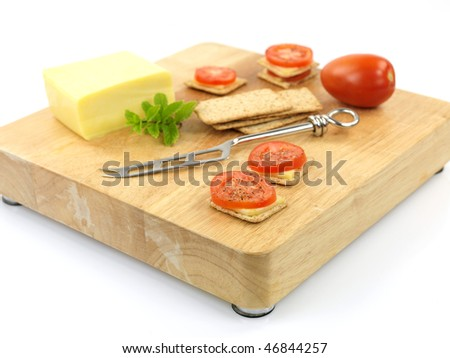 Savory snacks on a wood cutting board isolated against a white background