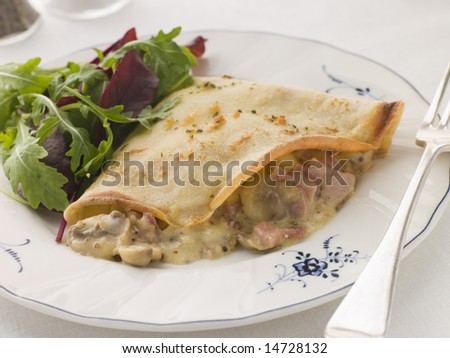 Savoury Pancake filled with Ham Cheese and Mushrooms with dressed salad - stock photo