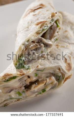 Savoury pancake with creamy mushroom and spinach filling. - stock photo