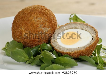 savoury scotch egg sliced in half with watercress garnish - stock photo