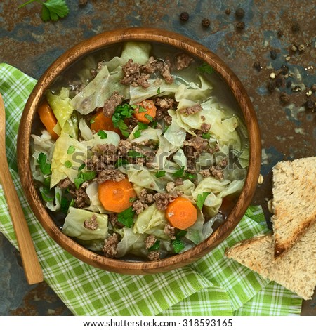 Savoy cabbage, carrot, potato and mincemeat stew or thick soup with parsley in wooden bowl, photographed overhead on slate with natural light (Selective Focus, Focus on the dish) - stock photo