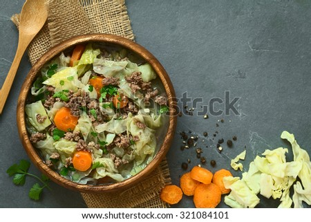 Savoy cabbage, carrot, potato, mincemeat stew or thick soup with parsley in wooden bowl, ingredients on the side, photographed overhead on slate with natural light (Selective Focus, Focus on the dish) - stock photo