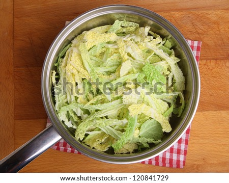 Savoy cabbage in stainless steel saucepan. - stock photo