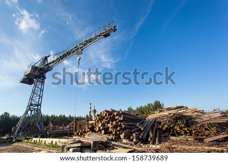 Saw mill with crane and stack of wood - stock photo