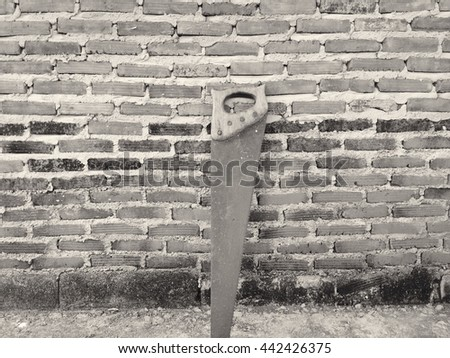 Saw on a red brick wall. Black and White