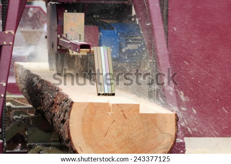 Sawing boards from logs with modern sawmill. - stock photo