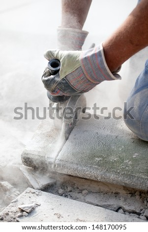 sawing stone with grinder hard working man in real action - stock photo