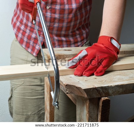 Sawing wooden pine board with the hand saw indoor composition - stock photo