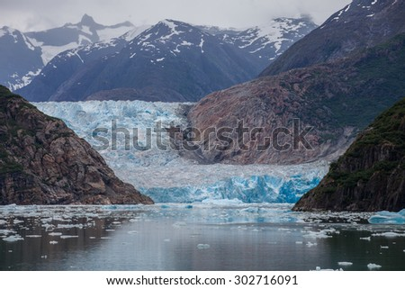 Sawyer Glacier, a huge tidewater glacier in Southeast Alaska is framed by its own reflection and the mountains it has carved through over time. - stock photo