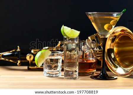 Saxophone and alcoholic drinks on a wooden table - stock photo