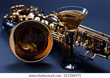 saxophone and martini with green olives , focus on foreground - stock photo