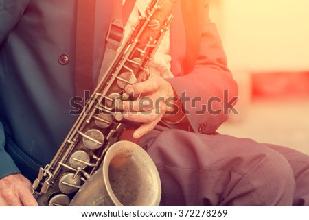 Saxophone in the hands of a street musician - stock photo