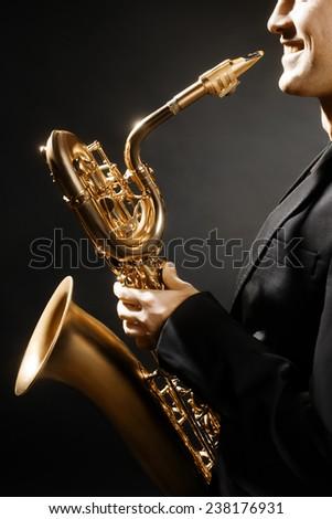 Saxophone man with music instrument Jazz saxophonist with Baritone sax - stock photo