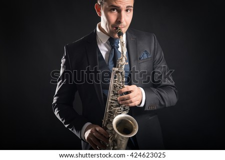Saxophone player man isolated against black background. Close up studio portrait.