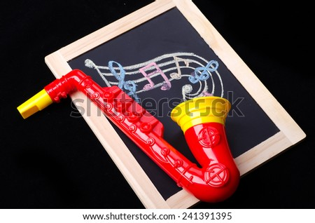 Saxophone toy with music note paint on the blackboard  - stock photo